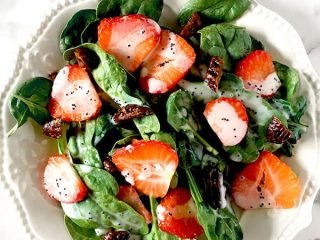 Strawberries and candied pecans on a bed of baby spinach drizzled with poppy seed dressing