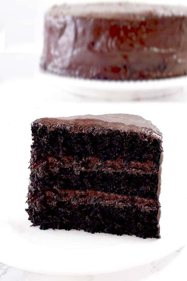 a slice of chocolate cake with a whole chocolate cake in the background