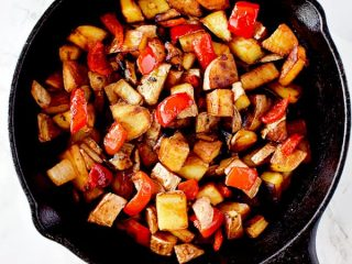 Breakfast hash of potatoes, peppers, and onions in a cast iron pan