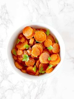 Moroccan carrot salad in a white bowl on a white marble counter