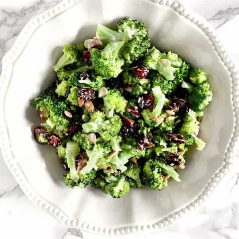broccoli salad with cranberries and sunflower seeds in a white bowl on a white marble counter