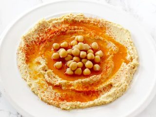 hummus in a plate on with oil, paprika, and chickpeas
