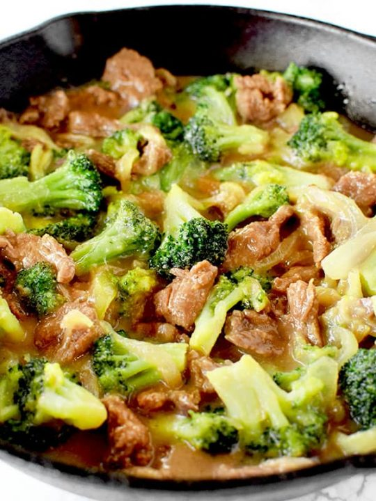 Beef and broccoli in a black pan on a white marble counter
