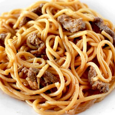 Beef lo mien on a white plate on a marble counter