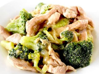 Chicken and broccoli on a white plate on a white marble counter