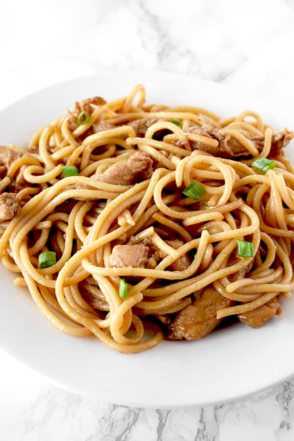 Chicken lo mein on a whit plate on a white marble counter