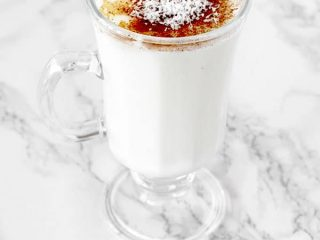 Cup of sachlav topped with cinnamon and coconut
