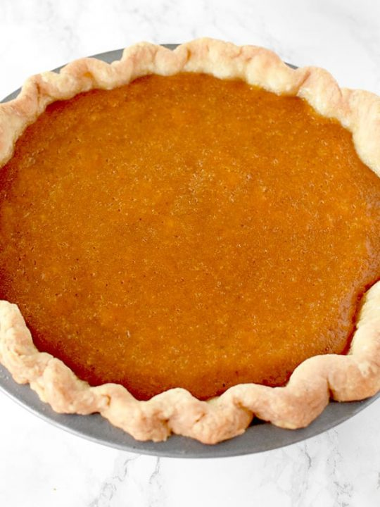 Dairy Free sweet potato pie in a homemade pie crust on a marble counter