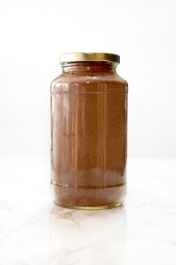 jar filled with dairy free chocolate cake mix on a marble counter
