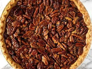Dairy free pecan pie sitting on a white marble counter