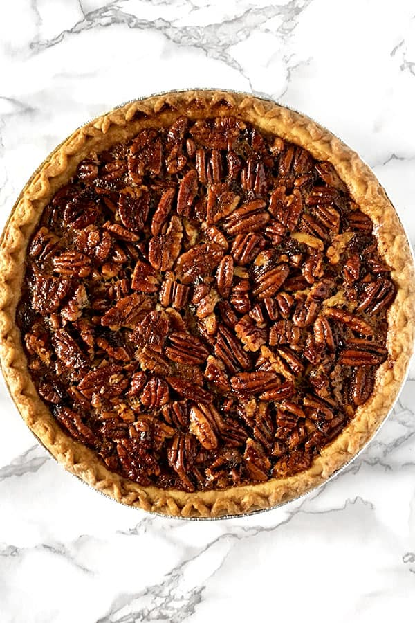 pecan pie without corn syrup sitting on a white marble counter
