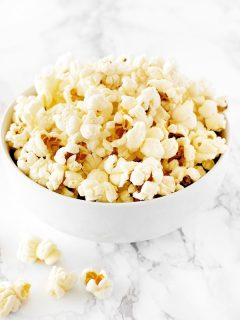 Kettle corn in a white bowl on a white marble counter