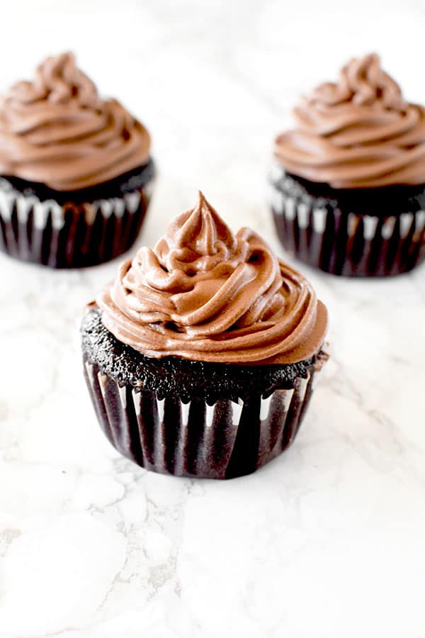 Three chocolate cupcakes with chocolate frosting on a white marble counter
