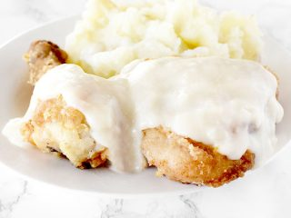 Maryland fried chicken with mashed potatoes on a white plate on a white marble counter