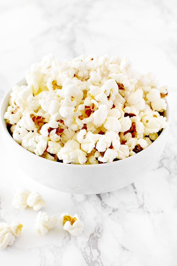 popcorn in a white bowl on a white marble counter