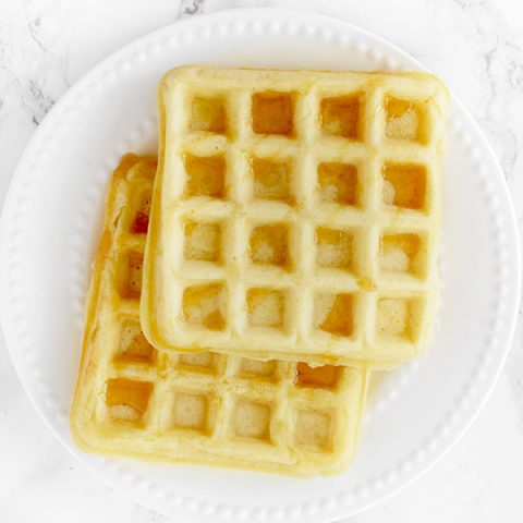 two waffles stacked on a white plate on a white marble counter