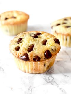 three chocolate chip muffins with oil on a marble counter