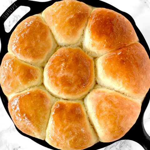 Dairy free dinner rolls in a cast iron skillet on a white marble counter