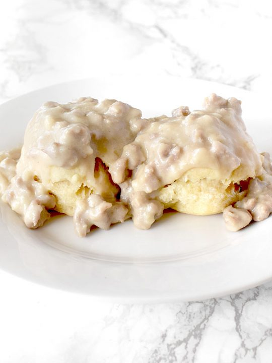 Dairy Free biscuits and gravy on a white plate on a white marble counter