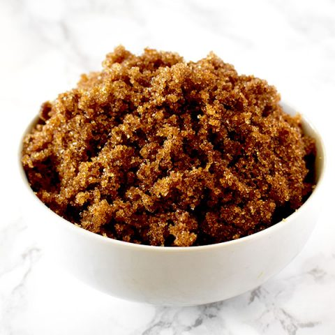 Dark brown sugar in a white bowl on a white marble counter