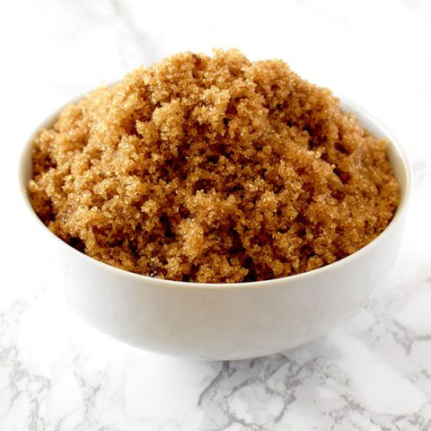 light brown sugar in a white bowl on a white marble counter
