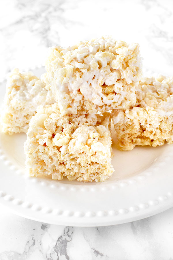 Dairy Free Rice Krispie Treats stacked on a white plate on a white marble counter