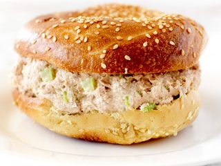 Tuna Salad in a bagel on a white plate on a white counter