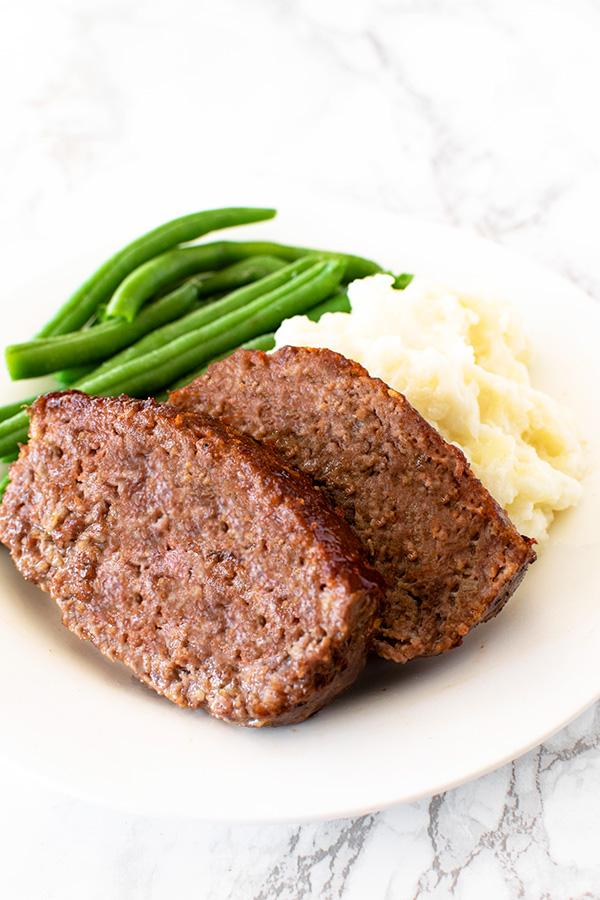 Meatloaf with green beans and mashed potatoes on a white plate on a white marble counter