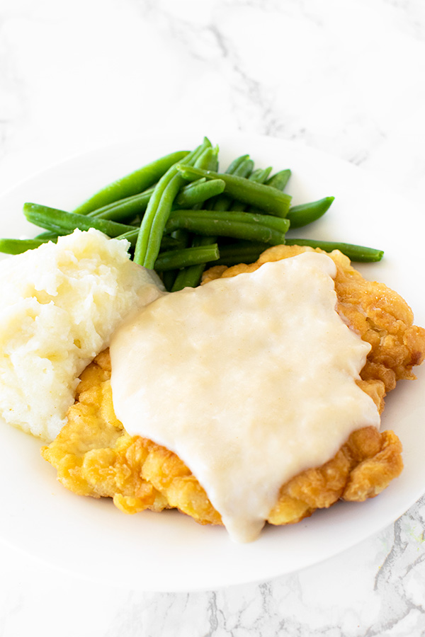 Chicken fried chicken with mashed potatoes and green beans on a white plate on a  white marble counter