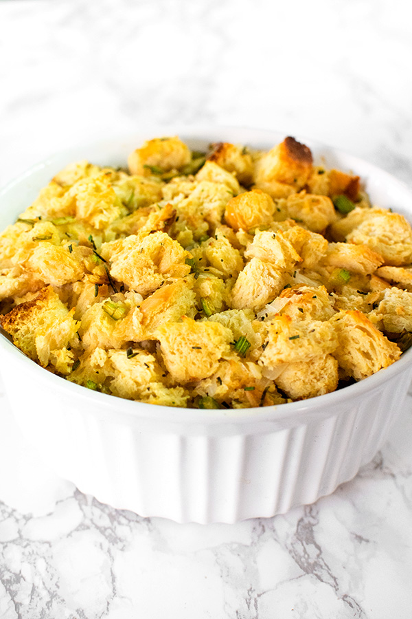 Dairy free stuffing or dressing in a white casserole dish on a white marble counter