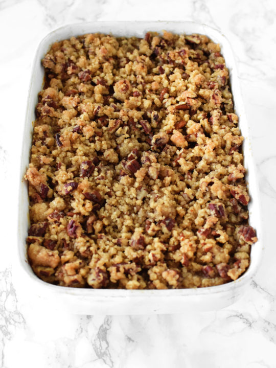 sweet potato casserole with pecans in a white casserole dish on a white marble counter
