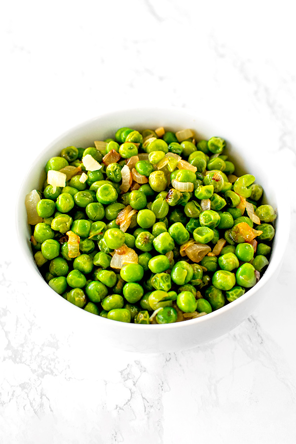 sauteed peas with onions on a white plate on a white marble counter