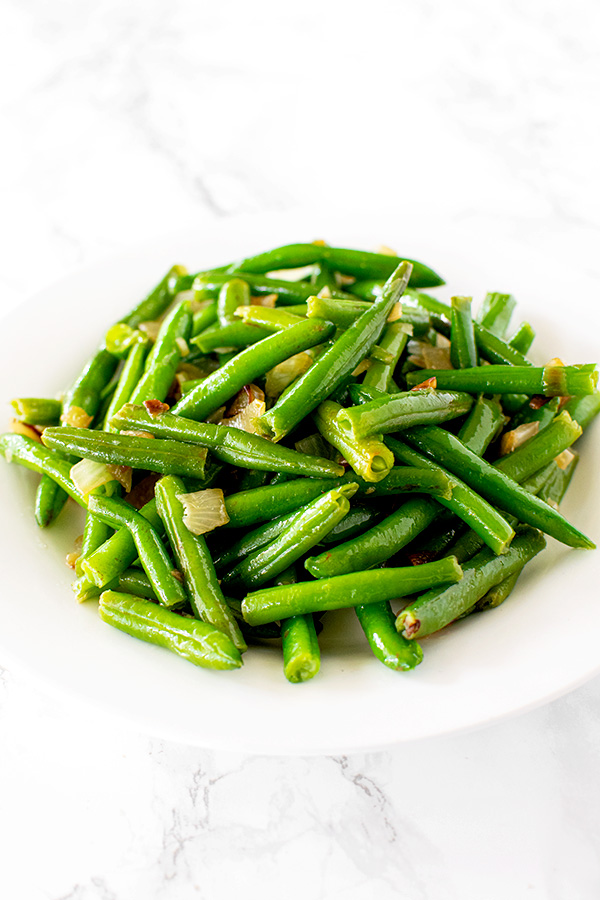 sauteed green beans with onions on a white plate on a white marble counter