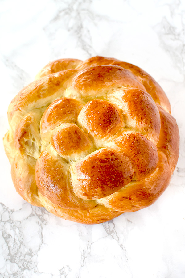 Round honey challah on a white marble counter